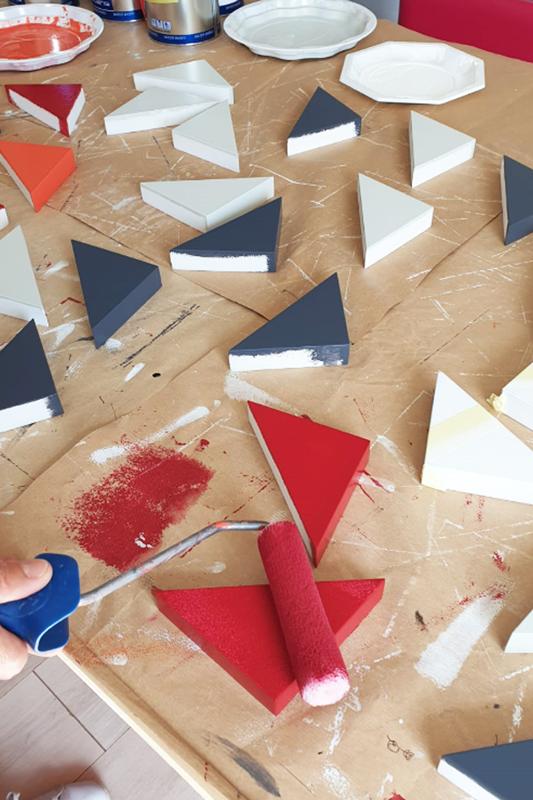 Console bois laqué à l'atelier : application à la main des couleurs du motif origami unique. Création et fabrication mobilier design Les Pieds Sur La Table Paris