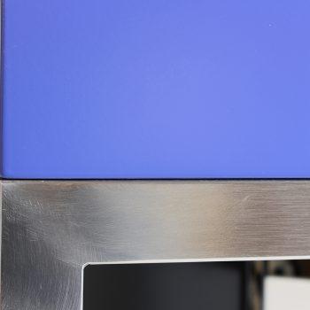Atelier de création de meubles contemporains Les PIeds Sur La Table, meubles design sur mesure, Etape du polissage d'une structure de meuble inox brossé par Sandrine Reverseau la créatrice. Détail angle estompé