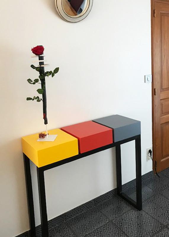 Console design sur mesure réalisée avec 3 cubes tiroirs laqués de couleurs solaires sur un pied en acier patiné. Console moderne d'entrée laquée Pied-Estal. Mobilier Les Pieds Sur La Table créateur et fabricant de meubles contemporains design sur mesure réalisation maison