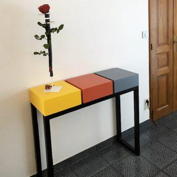 Console design sur mesure réalisée avec 3 cubes tiroirs laqués de couleurs solaires sur un pied en acier patiné. Console moderne d'entrée laquée Pied-Estal. Mobilier Les Pieds Sur La Table créateur et fabricant de meubles contemporains design sur mesure.