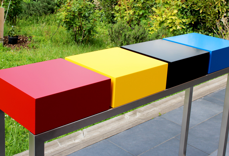 Console design connectée Plug&Pied sur mesure avec un choix de couleurs intenses : rouge piment, jaune soleil intense, bleu proche du cyan et noir sur un pied en inox brossé