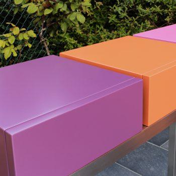 Console moderne décorative avec 3 tiroirs sur mesure à ouverture en façade. Console Pied-Estal avec un piétement en inox brossé. Tiroirs en couleurs finition laque contemporaine satinée, couleurs aubergine, orange pop, fuchsia. Photo détail. Une