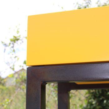 Console design sur-mesure, zoom sur le pied en acier patiné noi bruni de la console et le cube laqué de couleur jaune soleil intense. Mobilier Les Pieds Sur La Table créateur et fabricant de meubles contemporains design sur mesure.