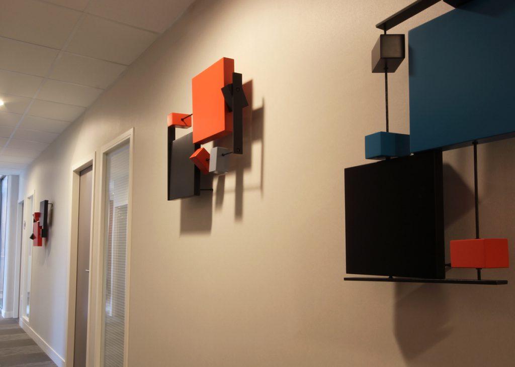 Décoration murale dans un couloir d'entreprise. Réalisation sur mesure par mobilier Les Pieds Sur La Table, meubles modernes design sur mesure, créations et fabrication sur mesure