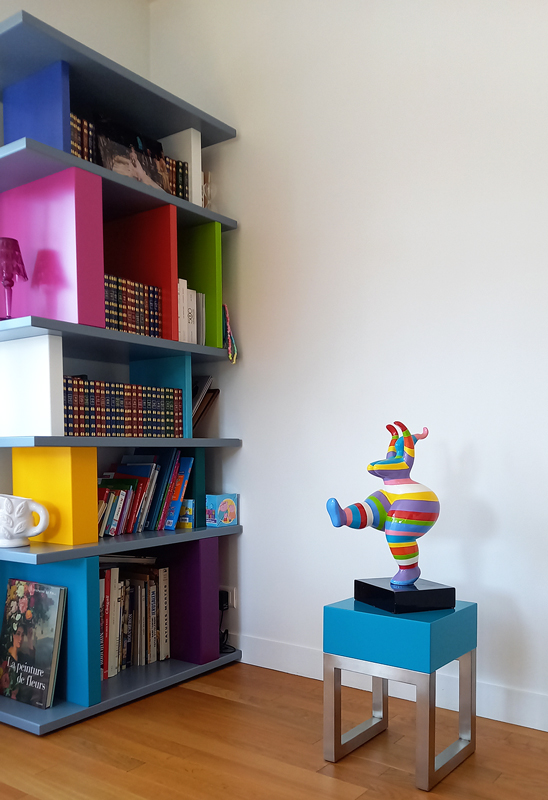 Le socle design en inox brossé et bois laqué turquoise est coordonné à la sculpture et à la bibliothèque Tu-Lis-Pied adjacente. Création mobilier contemporain Les Pieds Sur La Table